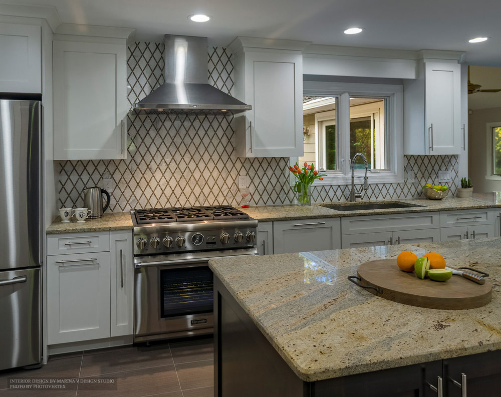 Kitchen interior with stainless steel appliances and granite top island