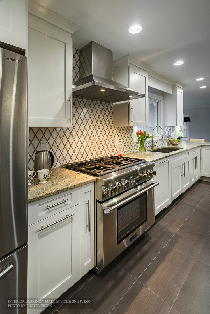 Kitchen area with stove and white cabinetry
