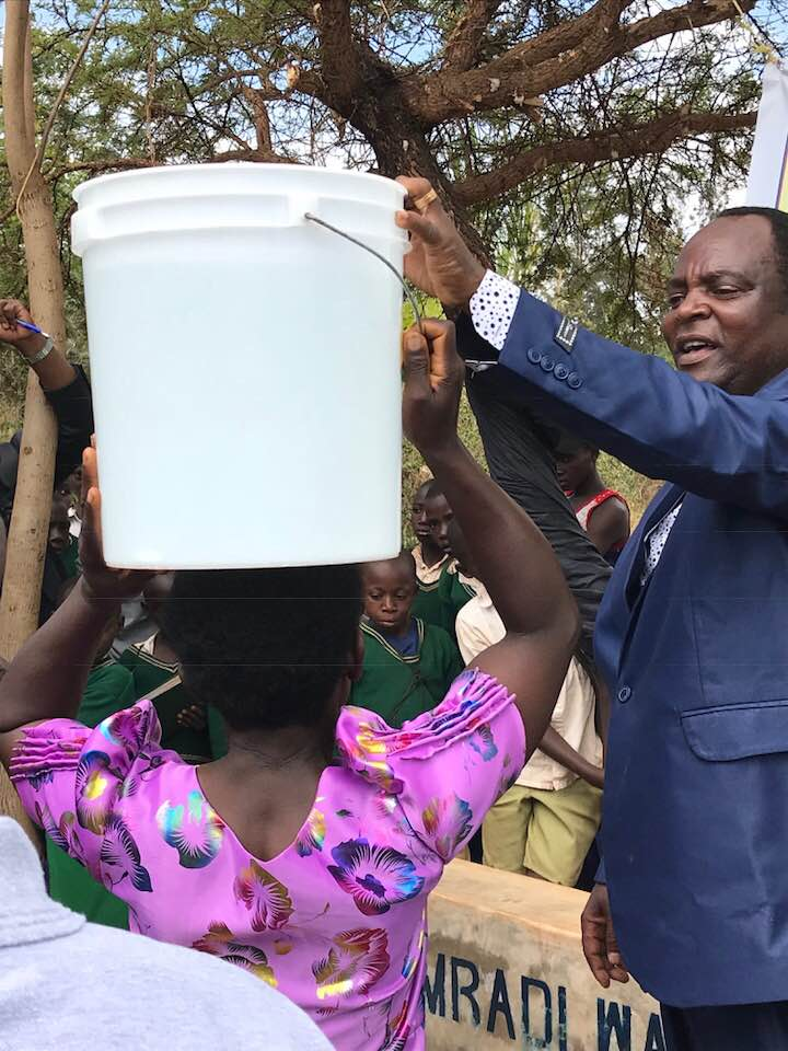 District Commissioner lifting a full water bucket on the head of a woman at the inauguration