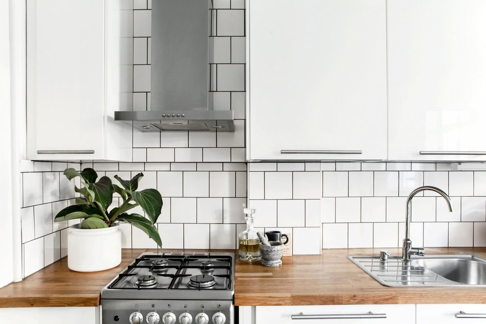 Square white tile backsplash with dark grout
