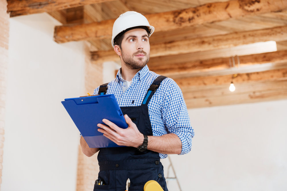 Builder-in-hardhat-with-clipboard-and-pencil-indoors-585504376_1258x838.jpeg