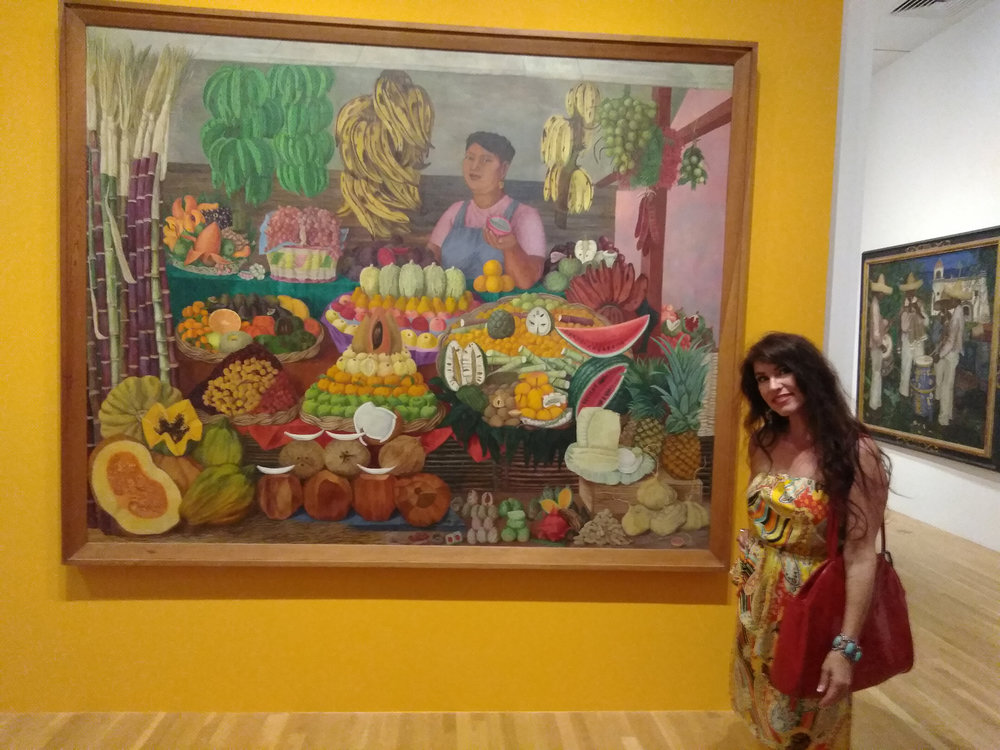 """This was one of my favorites. """"The Fruit Seller"""" by Olga Costa. The detail and colors are amazing. And I was so impressed with the bold, bright wall colors for the show. They were such a complement to the art."""