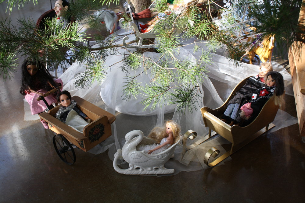 Dolls in sleds around the studio tree