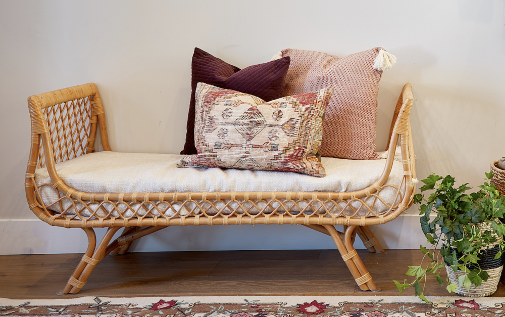 This bench is practical in that it provides a place to put on shoes but it also packs a bunch with its bold boho design and pillow styling.