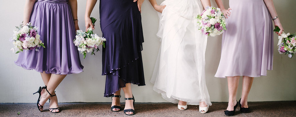 bridesmaids wearing shades of lilac and purple with matching flower bouquets