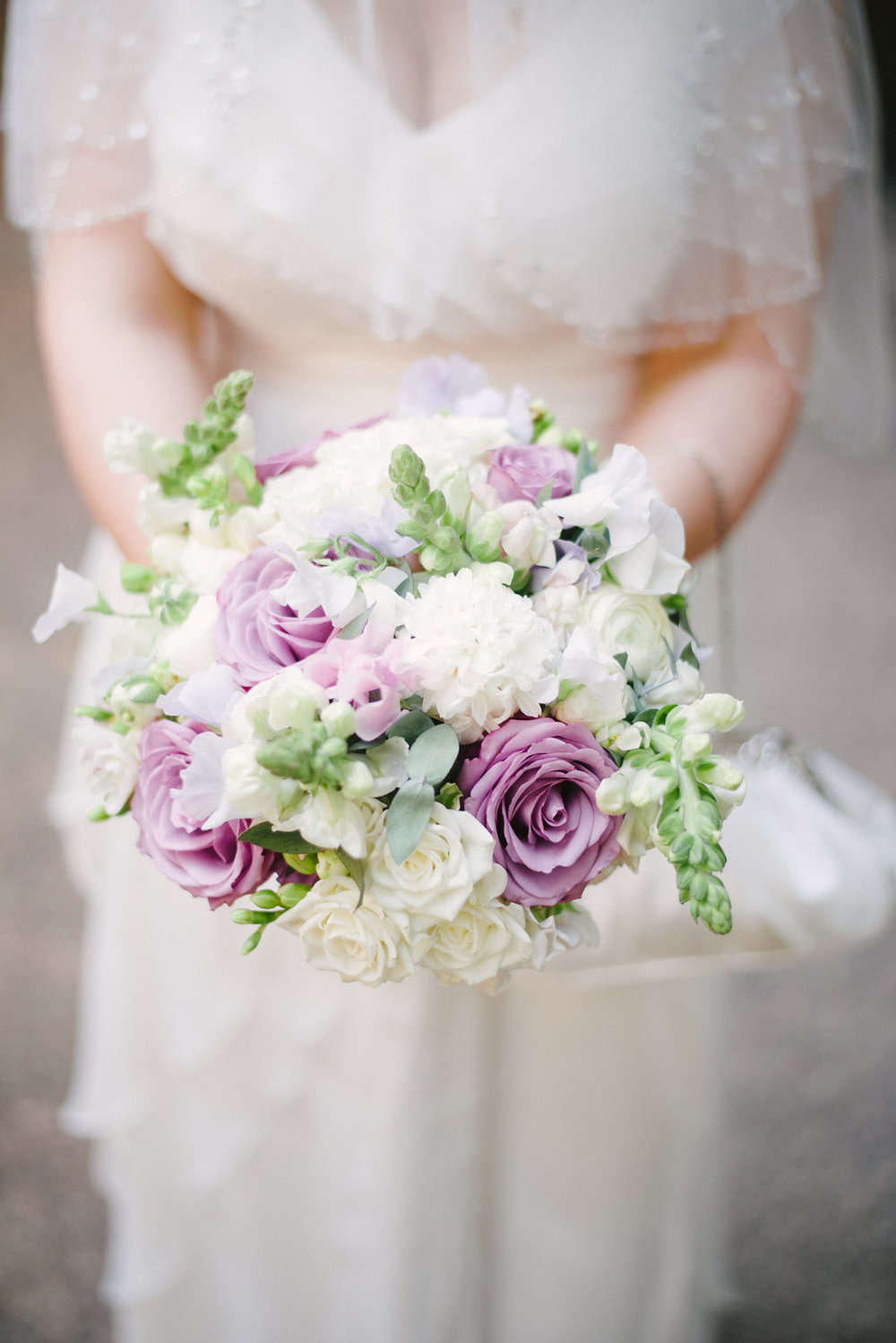 brides bouquet in white and lilac spring flowers to include roses, snapdragons and fragrant freesia