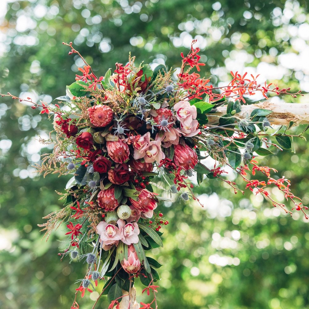wedding arbour floral piece in burgundy, pink and blue flowers
