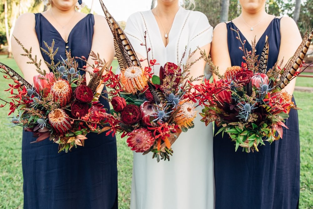 bride and bridesmaids bohemian inspired bouquets to complement navy dresses