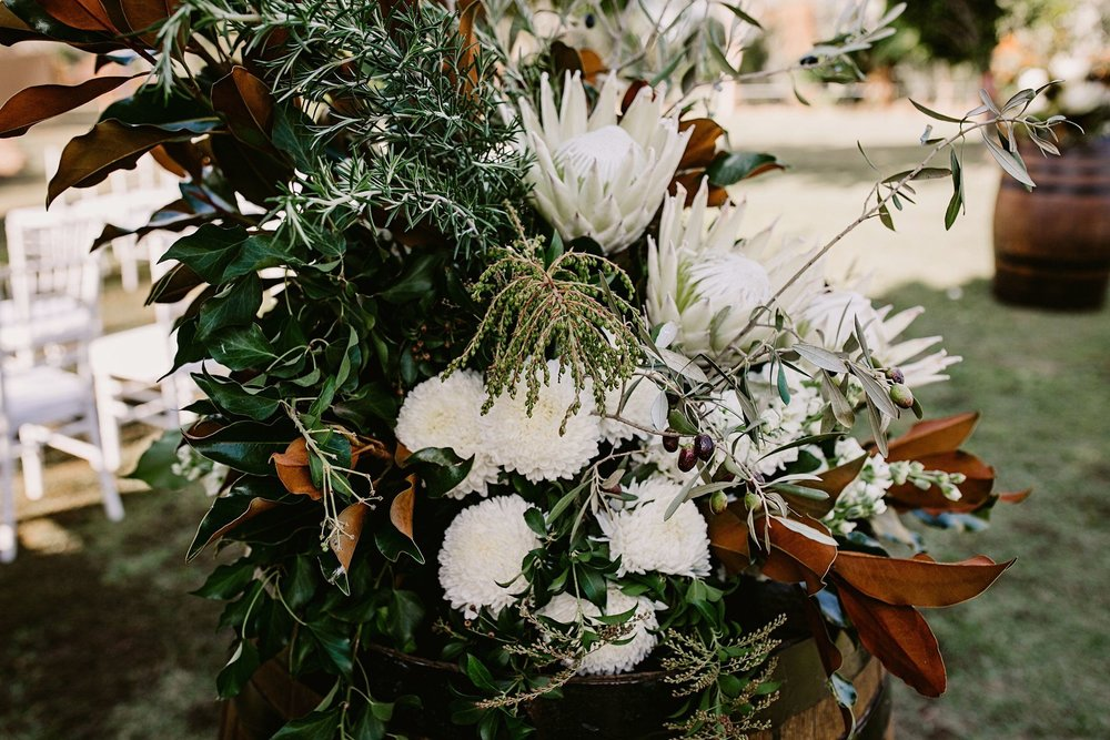 king proteas, white chrysanthemum flowers on barrel create at wedding entrance feature