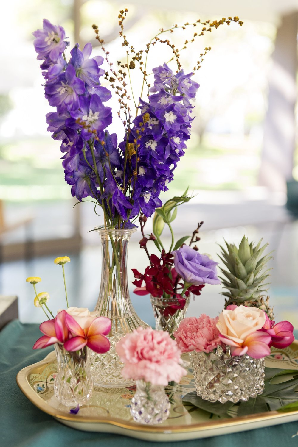 crystal vases topped with delphiniums, roses and pineapples