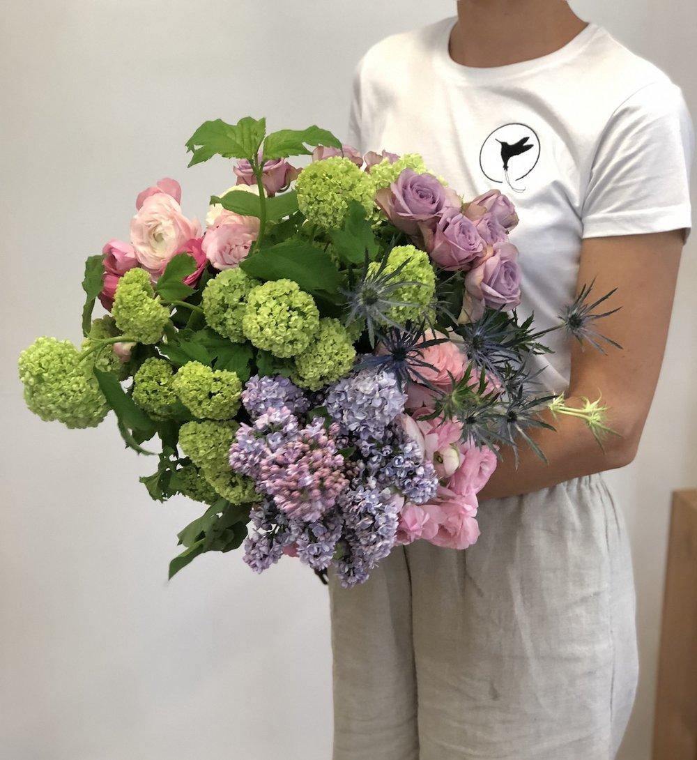 huge spring bouquet designed by Darwin florist Beija Flor including guelder rose, lilac, ranunculi, sea holly and garden rose