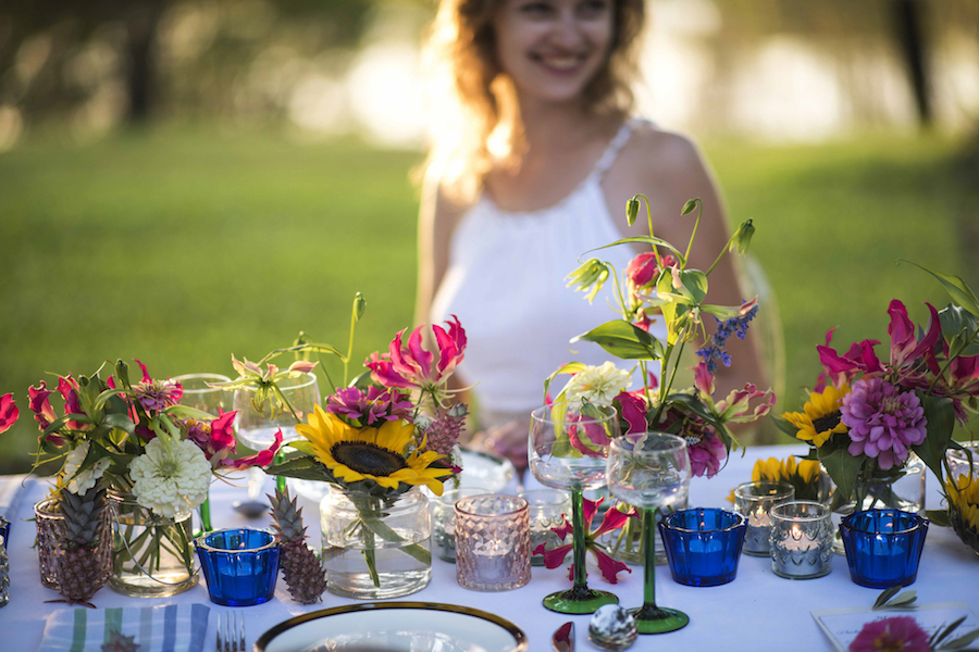 colourful candle votives and stemware complete this flower filled tablescape