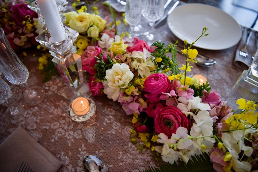 a summery floral garland, snakes across the guest tables, flowers include ranunculus, hydrangea, tulips, dancing lady orchids (oncidium) and fragrant geranium greens, created by Darwin florist, Beija Flor
