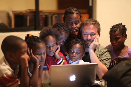 Orphan children help Doug with his computer posts.