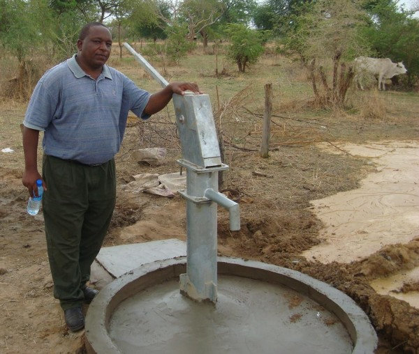 PPF field manager stands next to a new PPF well for Darfur refugees.