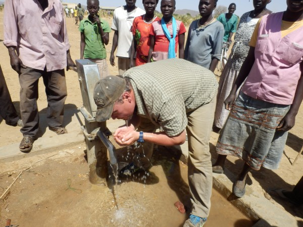 PPF's Brad Phillips takes a drink from a repaired well in the Nuba Mountains.