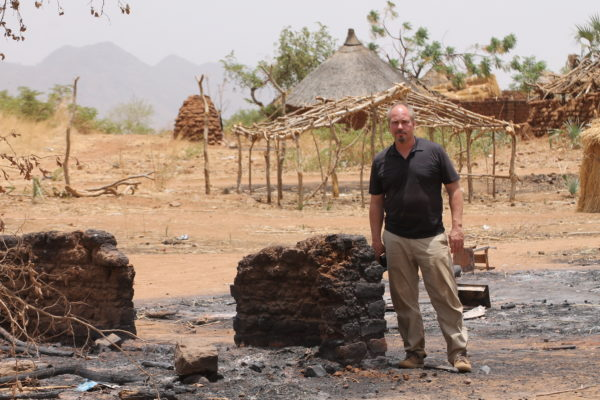Brad stands next to a burned home.