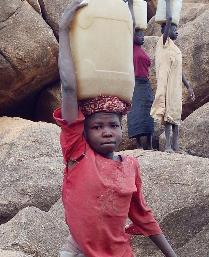 11-year-old Rhemas carrying water to her family