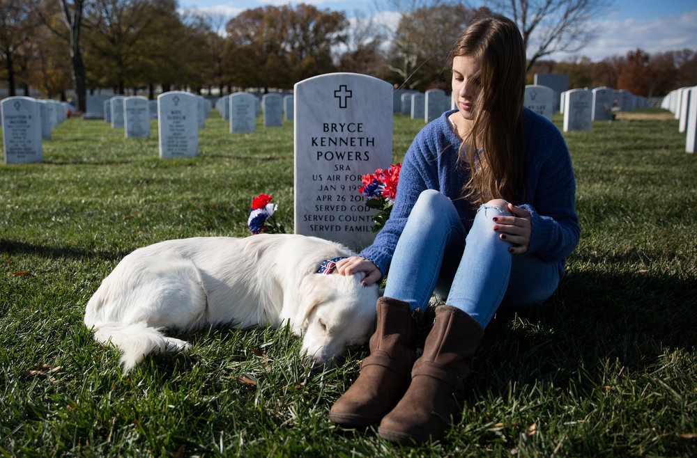 Madi Powers sits near the grave of her brother, Senior Airman Bryce Powers at Arlington National Cemetery.  SRA Powers died in 2013 as the result of a car crash during his deployment in Japan. The dog is a service dog named after her brother who is being trained by her to support veterans with PTSD. Taken on November 25, 2017.