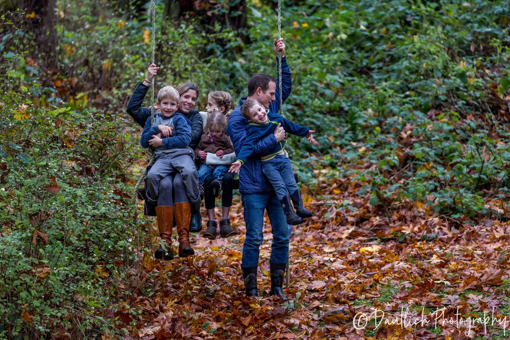 The Young family on a tree swing in their garden during their documentary family portrait session.