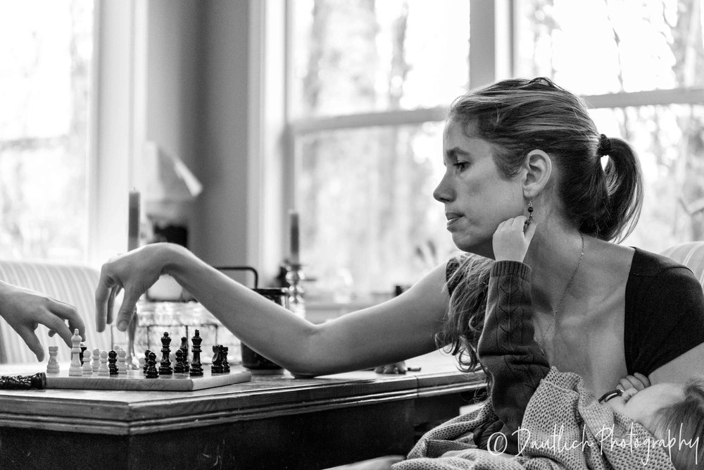 Mom playing chess with one child while baby pulls on her earring.