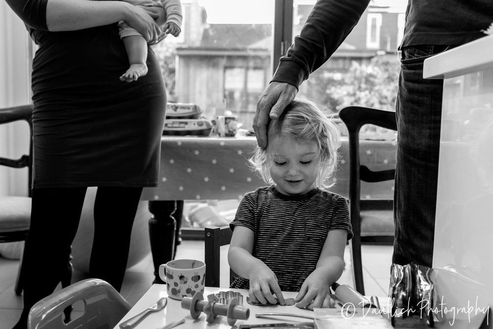 Family in the kitchen. Lila is playing at the craft table while dad gently touches her head and mom and baby cleo are in the background.
