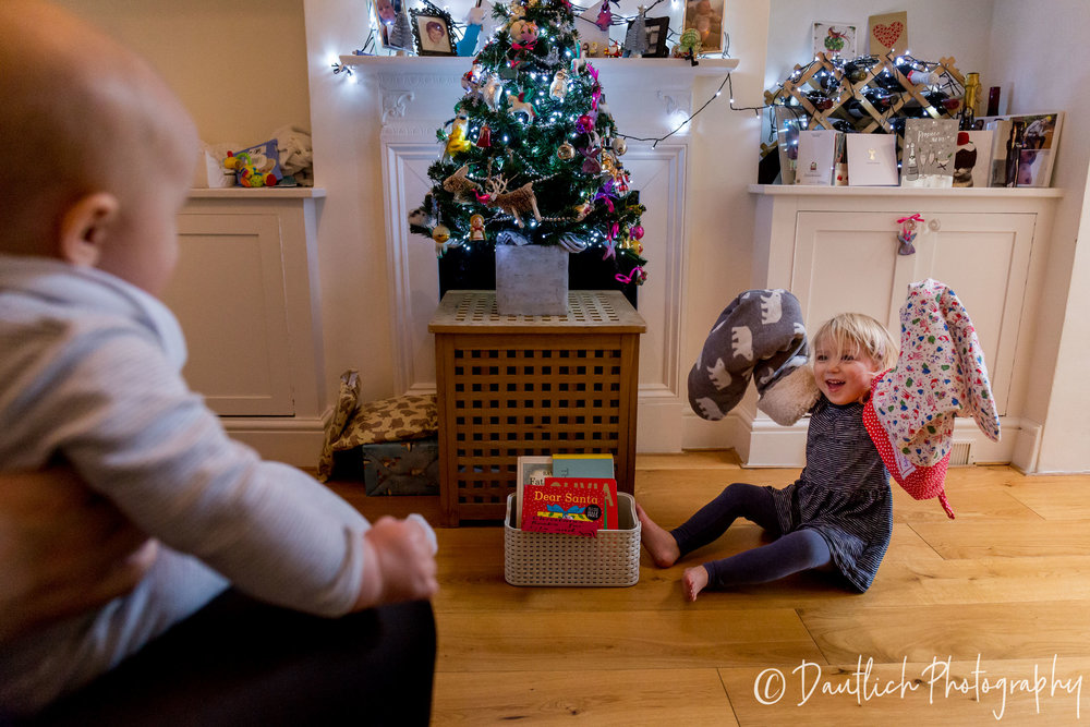 Lila is being silly and putting the Christmas stockings on her arms to entertain her sister Cleo.