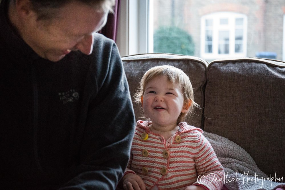 Nick and Hazel laugh together on the sofa in Haywards Heath.