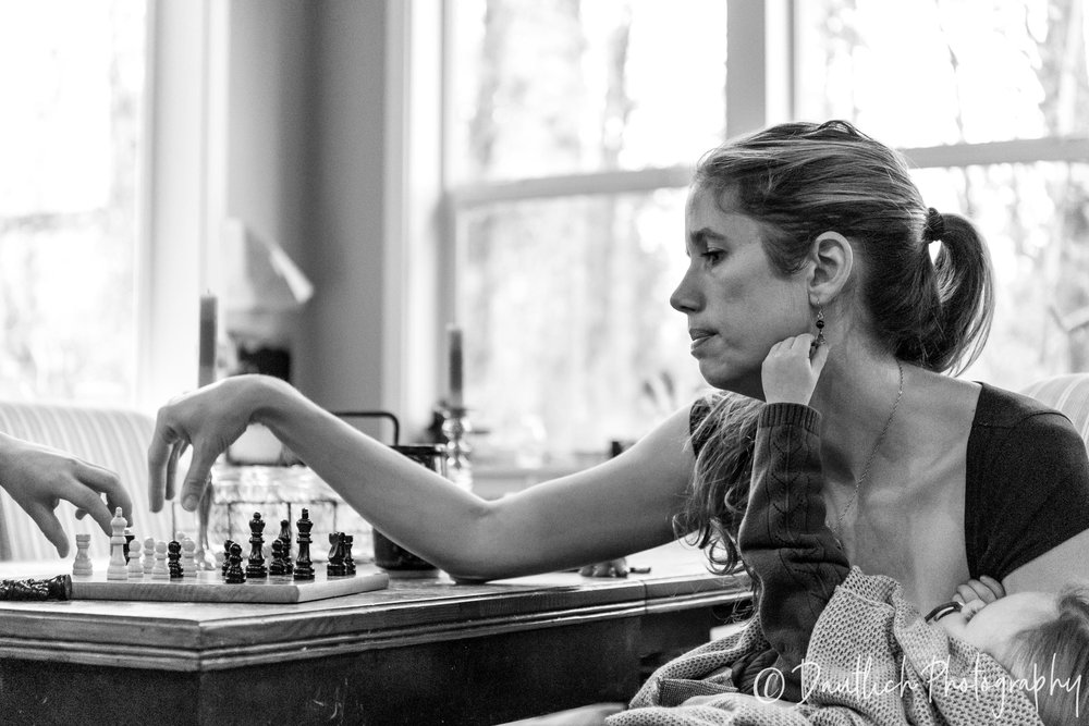 Mom playing chess with her child as baby pulls on her earring.