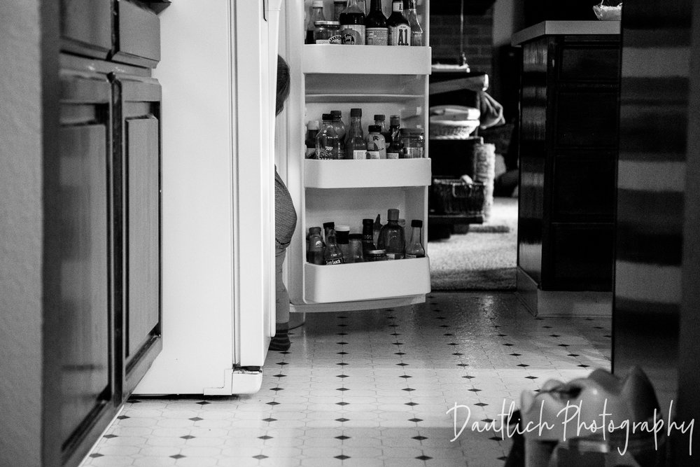 Mischievous toddler stands in the open refrigerator looking for items to pull out.
