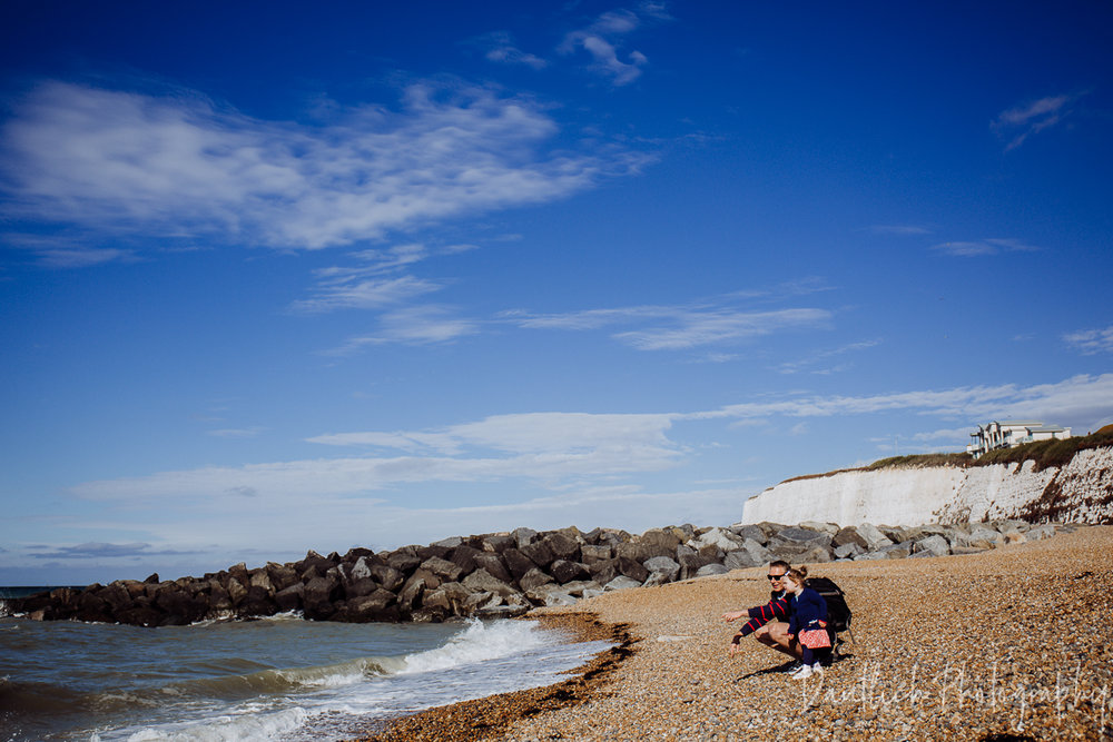 Hazel and Nick throwing rocks into the sea at Rottingdean Beach outside of Brighton.