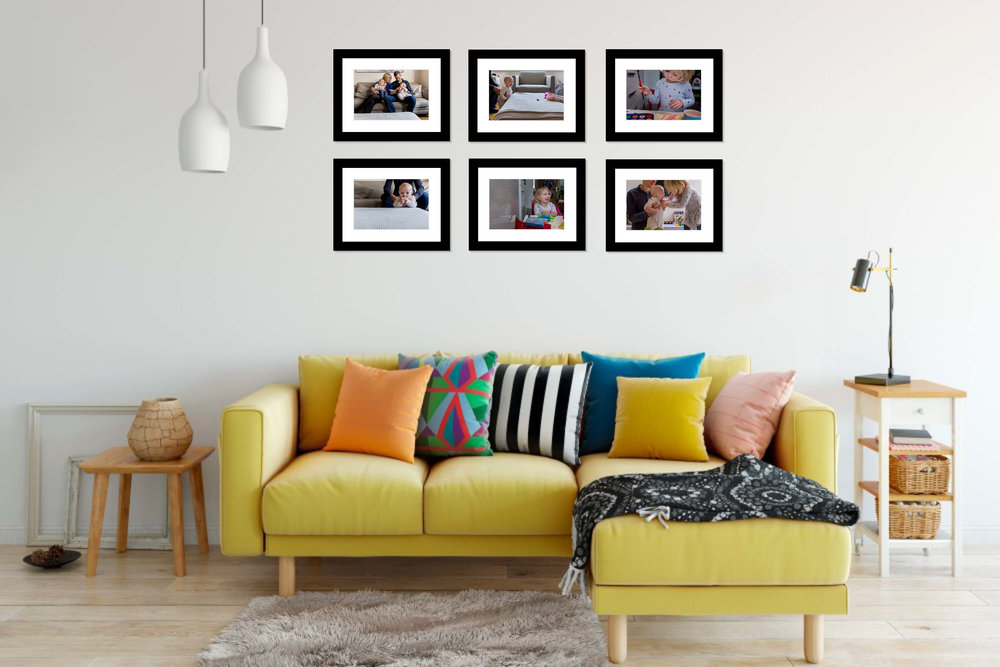 Client sample living room with modern storytelling family session framed prints on the wall.