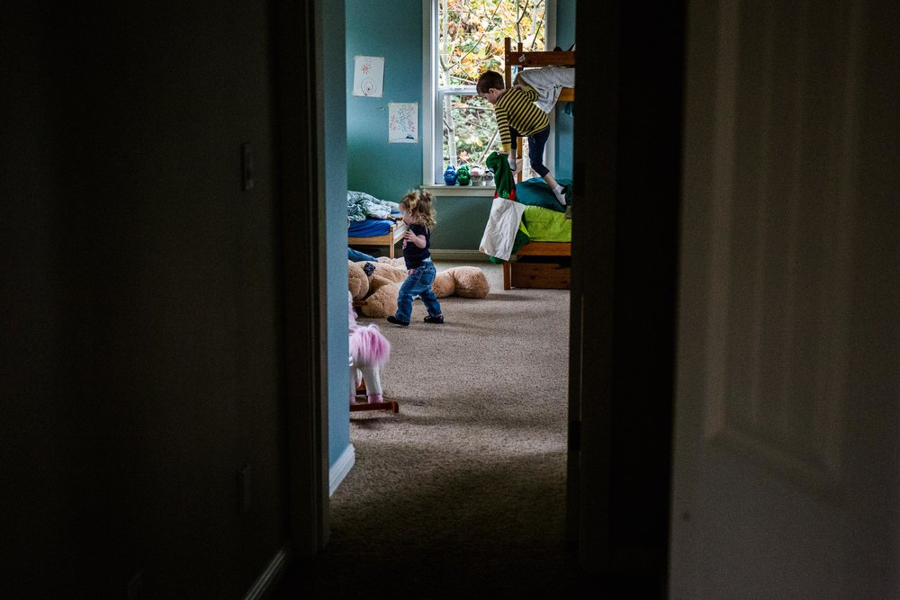 Toddlers jumping on bunk bed and running around in room during a day in the life photography session.