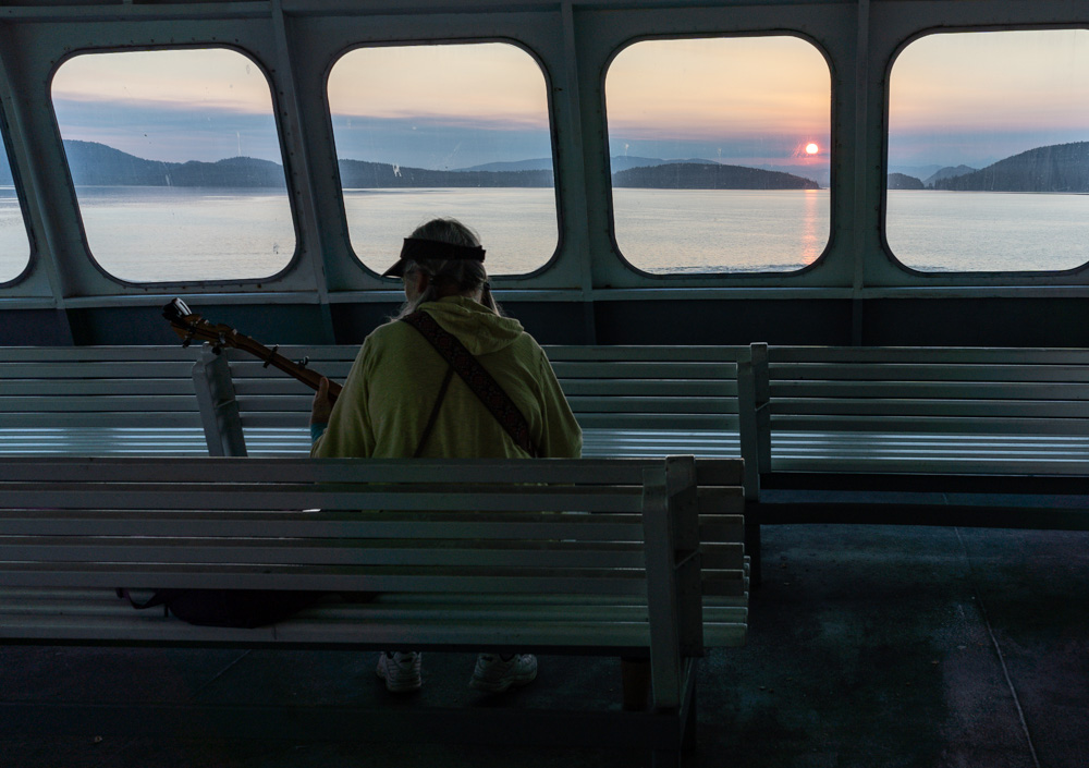 Amazing lady playing here banjo on the ferry during sunrise