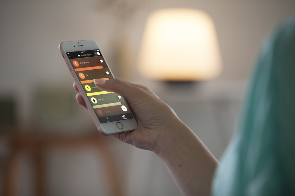 Woman holding smartphone controlling Philips Hue Lighting through app ambience white 2.jpg
