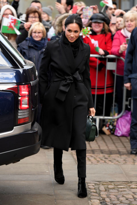 Markle wore a black  Stella McCartney coat , trousers by the Welsh fashion house  Hiut Denim  and a  DeMellier 'Mini Venice' bag  for her first royal visit to Cardiff.