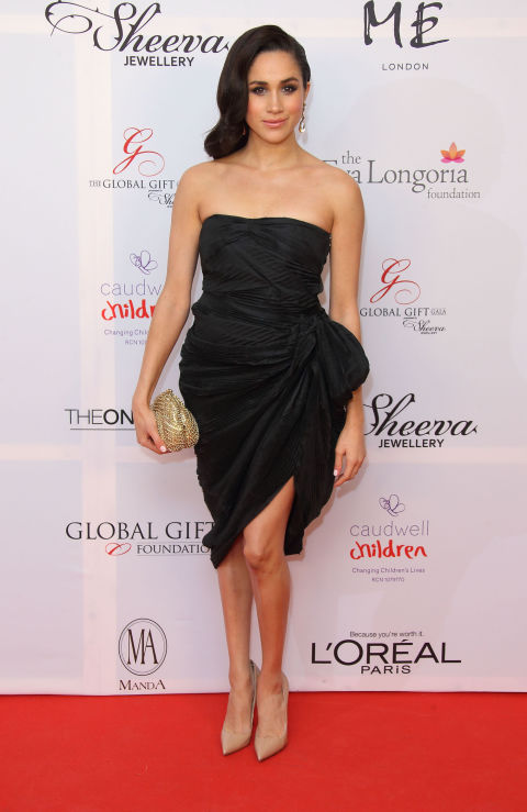 At the London Global Gift Gala at ME Hotel, November 2013 wearing a black asymmetrical dress, nude pumps and gold clutch
