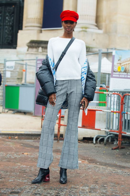 Model Tami Williams wears a red newsboy cap and a black adidas bomber jacket over a white sweater with grey houndstooth trousers, outside the  Chanel show  via Refinery29