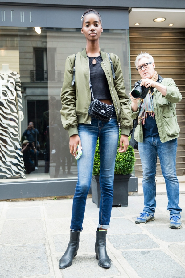 Exiting a  Haute Couture  Autumn/Winter 2016 show, model  Tami Williams  looked graceful in a casual off-duty look. She paired a green bomber jacket with a black crop top and jeans, as well as black ankle boots and a studded black shoulder bag. Still wearing the hair crown and gold makeup from her latest show, Tami makes this street cool outfit elegant via The Front Row View.