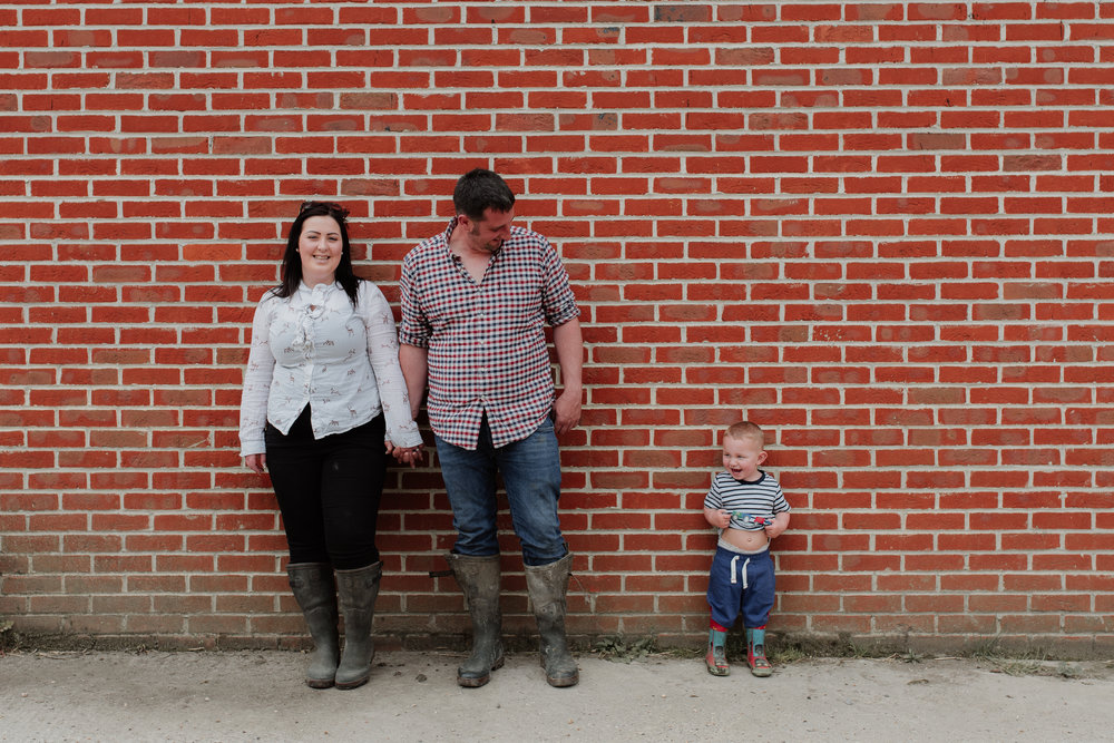family in front of brick wall