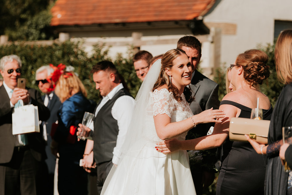 Bride greeting wedding guests Sonning