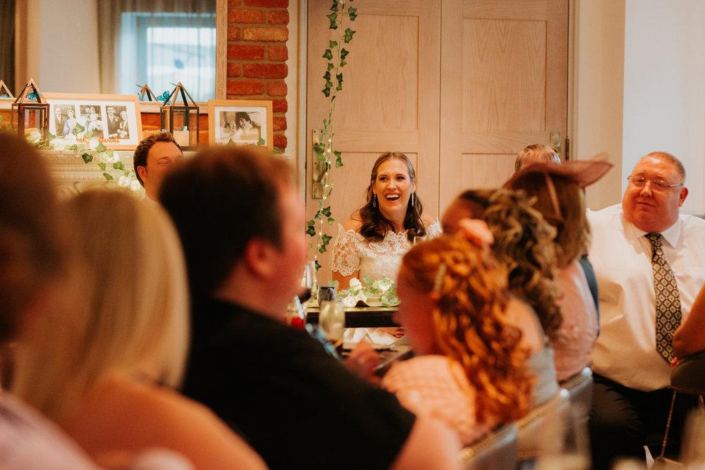 Bride laughing at wedding speech