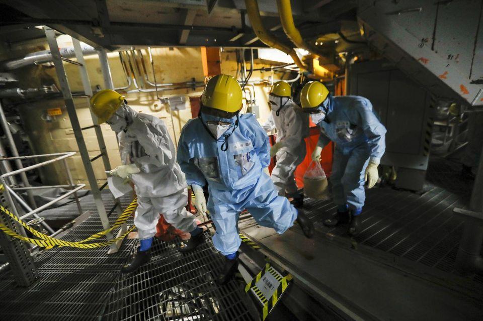 Des salariés de la société Tepco sortant du réacteur 5, le 20 novembre.Photo Kimimasa Mayama. Maxppp