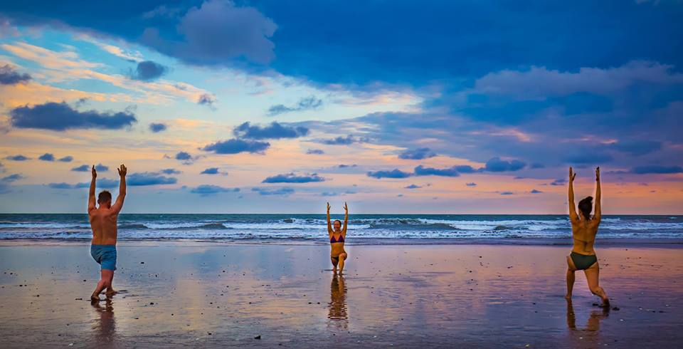 3 people stretching in sun salutation pose on a beach at sunrise