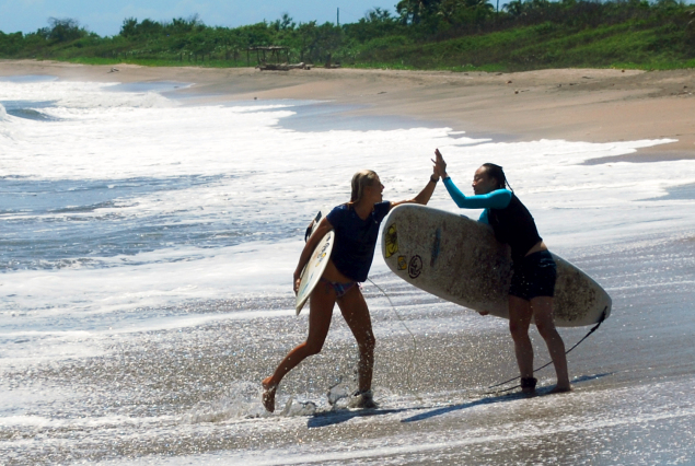 2 female surfers with surf boards high five on a beach