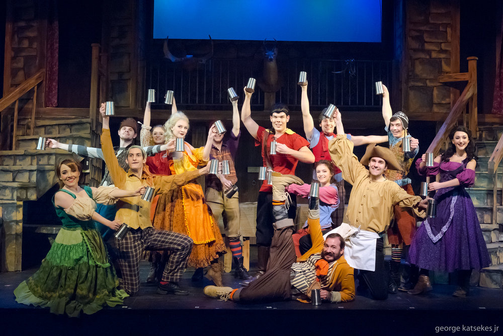 """Gaston (Tim Albrechtson, center standing) is toasted during the mug routine during the song """"Gaston"""" in a scene from Sunset Playhouse's """"Disney's Beauty and the Beast."""" LeFou (Jim Donaldson), Gaston's sidekick, is front and center."""