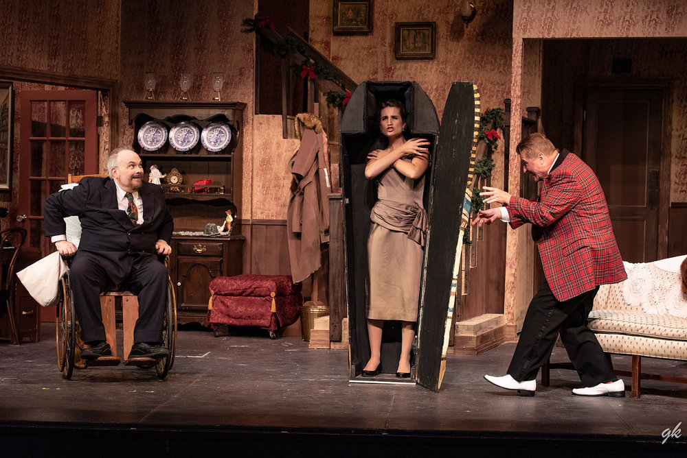 "Actress Lorraine Sheldon (Kat Zilka) creates a dramatic moment as she gets into a gift Egyptian sarcophagus delivered to Sheridan Whiteside (Hal Erickson), left, while Sheridan's friend Banjo (Jim Stahl) gets ready to close it up in a scene from Sunset Playhouse's ""The Man Who Came to Dinner."""