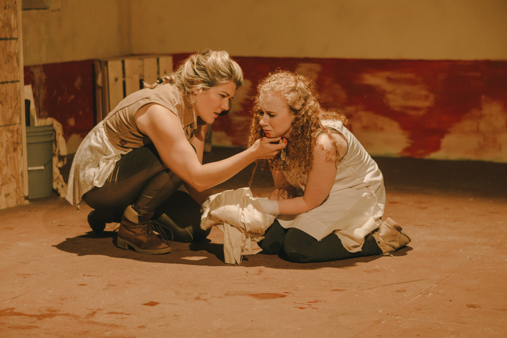 "Marcus (Jessica Trznadel), brother of Titus, comforts Lavinia (Alexis Furseth) after her brutal attack in the woods in a scene from Voice Found Repertory's ""Titus Andronicus."""