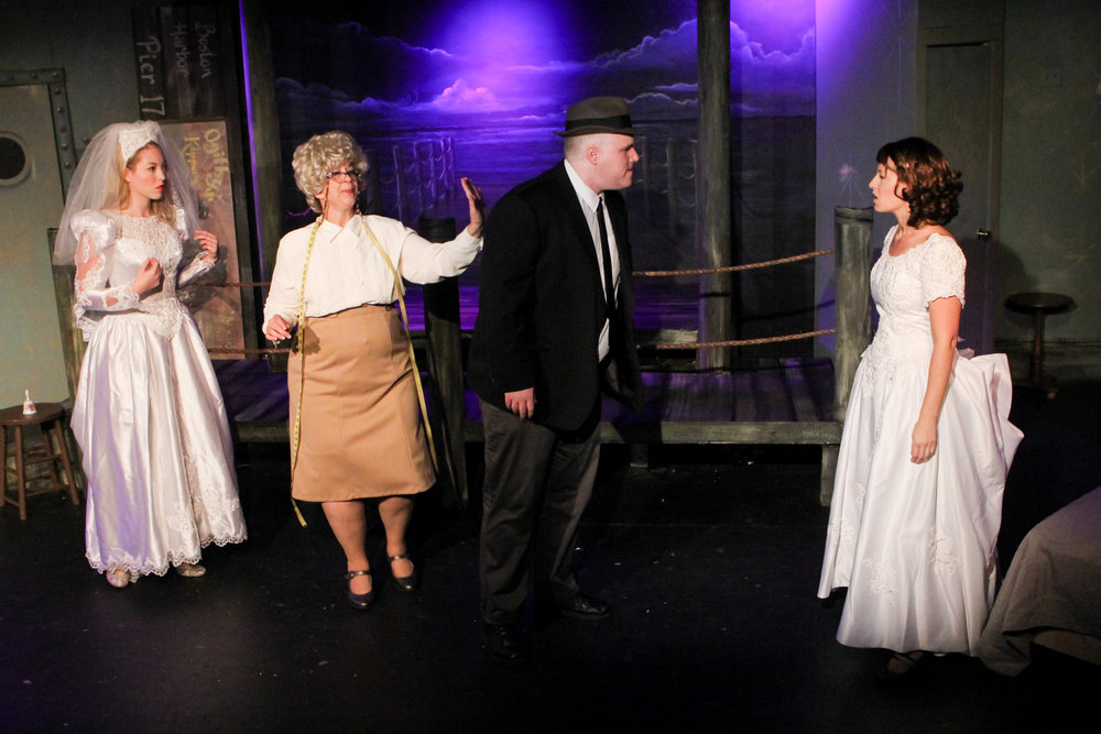 "G-man Frank (John Reilly) confronts his fiancé Maggie (Cayla Anderson) at a dress shop where Lynn (Stephanie Nilsen) is also trying on dresses suggested by the shop's owner (Rebecca Richards) in a scene from Lake Country Playhouse's ""Red Herring."""