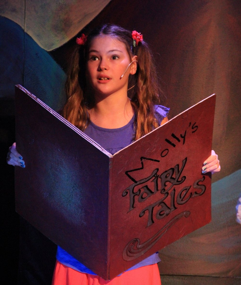"""Maya Kalush as Molly reads from her book of fairy tales in """"Molly's (Mostly) Accurate Retelling of Fairytales."""""""
